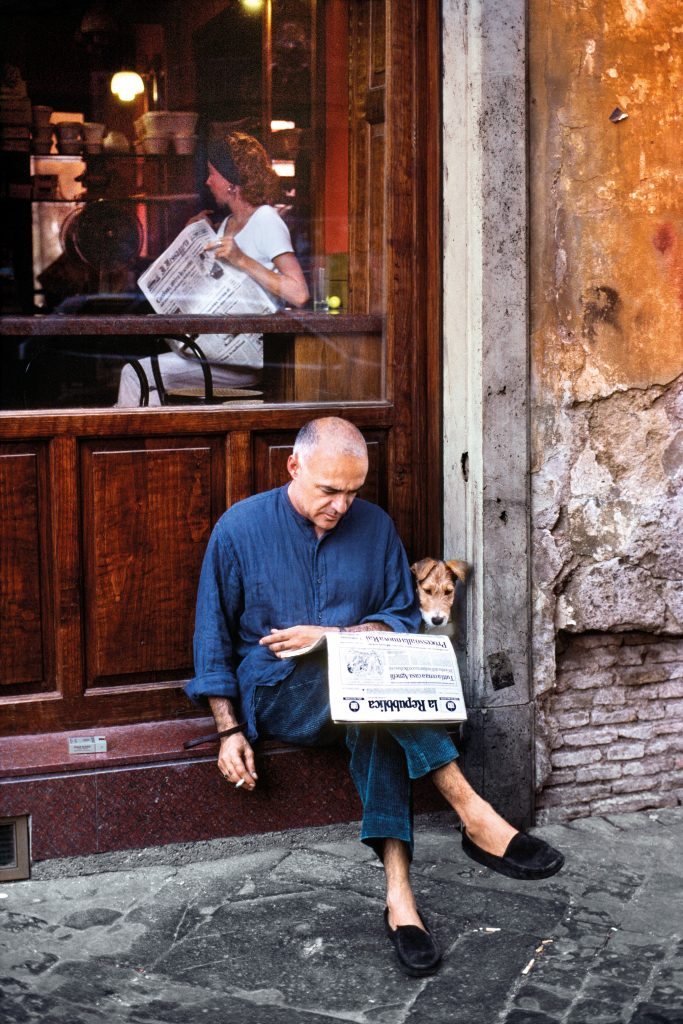 01094_19, Rome, Italy, 10/1994, ITALY-10089. A man reads the newspaper with his dog outside a restaurant. CAPTION: Man Reads Newspaper with Dog. Rome, Italy, 1994. IG: Reading is the sole means by which we slip, involuntarily, often helplessly, into another's skin, another's voice, another's soul. – Joyce Carol Oates 06/24/2016 - ARCHIVED? IG: I photographed this man and his dog reading the newspaper in Rome, Italy. 01/19/2017 - ARCHIVED Reading_Book pg. 45 Retouched_Sonny Fabbri 3/30/2016, Scott Mclane, Eolo Perfido 05/10/2019